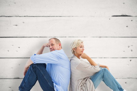 Upset mature couple not talking against white wood Stock Photo