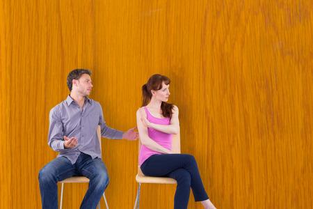 argument: Sitting couple having an argument against wooden pine table