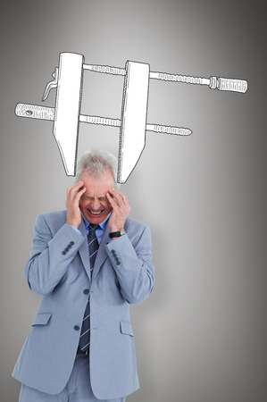 wincing: Man  with headache against grey vignette Stock Photo