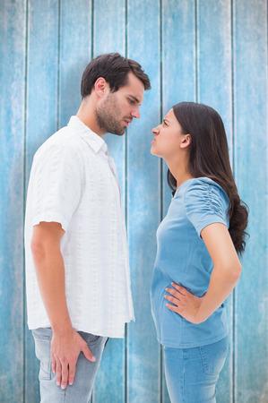 pareja enojada: Pareja enojado mirando el uno al otro en contra de tablones de madera