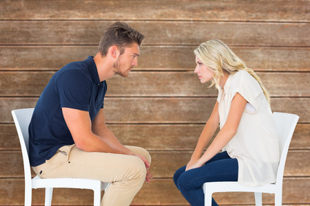 accusing: Young couple sitting in chairs arguing against wooden planks background