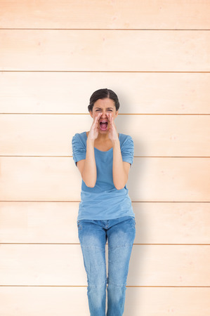pale wood: Pretty brunette shouting against wooden background in pale wood Stock Photo