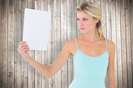 angry blonde: Angry blonde holding a sheet of paper against wooden planks background Stock Photo