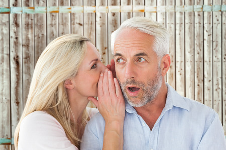 pale wood: Woman whispering a secret to husband against wooden background in pale wood Stock Photo