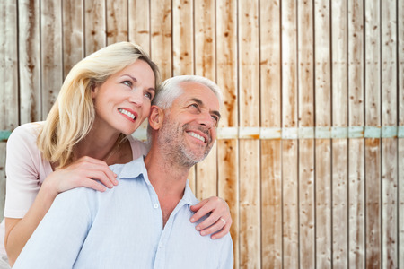 pale wood: Smiling couple embracing and looking  against wooden background in pale wood Stock Photo