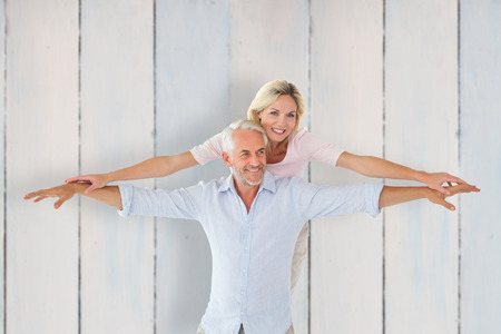 arms out: Smiling couple posing with arms out against wooden planks
