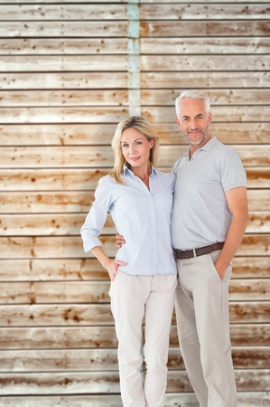 pale wood: Happy couple standing and smiling at camera against wooden background in pale wood