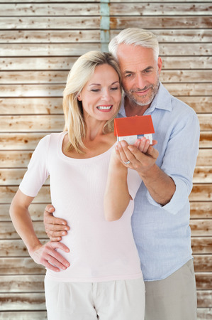 pale wood: Happy couple holding miniature model house against wooden background in pale wood