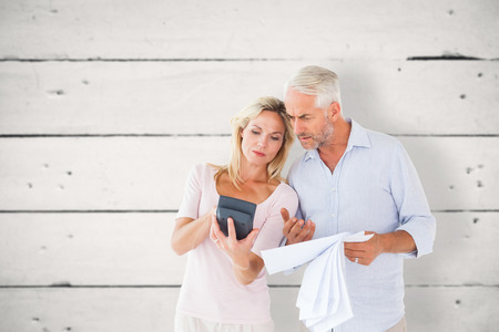 figuring: Anxious couple working out their bills against white wood Stock Photo