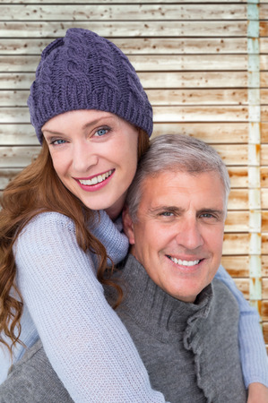 warm clothing: Happy couple in warm clothing against faded pine wooden planks Stock Photo