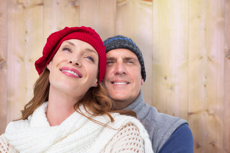warm clothing: Happy couple in warm clothing against wooden background in pine