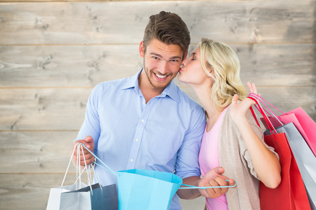bleached: Attractive young couple holding shopping bags against bleached wooden planks background Stock Photo
