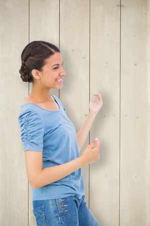 air guitar: Pretty brunette playing air guitar against bleached wooden planks background