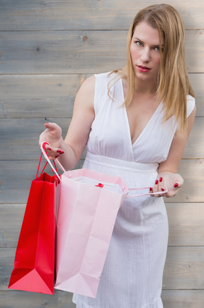 attractive gorgeous: Blonde with shopping bags against pale grey wooden planks Stock Photo