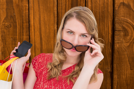 telephoning: Pretty blonde in sunglasses holding shopping bags against overhead of wooden planks Stock Photo