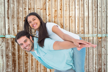 pale wood: Happy casual man giving pretty girlfriend piggy back against wooden background in pale wood