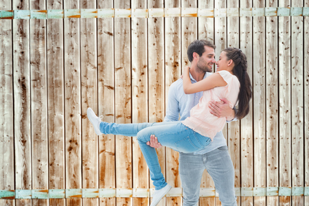 pale wood: Attractive young couple having fun against wooden background in pale wood