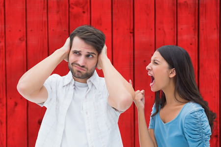 outraged: Angry brunette shouting at boyfriend against red wooden planks