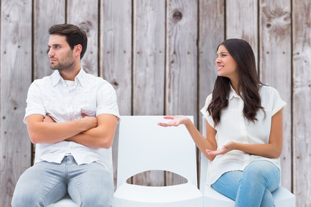 pleading: Brunette pleading with angry boyfriend against wooden planks Stock Photo
