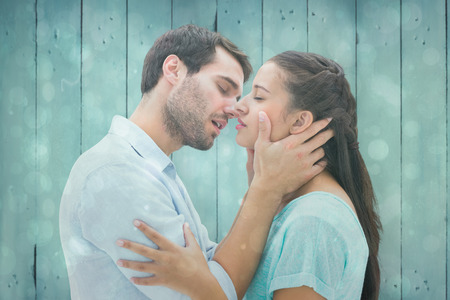 Attractive young couple about to kiss against blue abstract light spot design