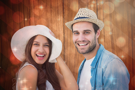Happy hipster couple smiling at camera against light design shimmering on red photo