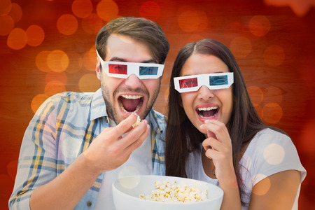 Attractive young couple watching a 3d movie against close up of christmas lights photo