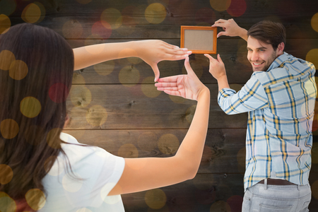 putting up: Happy young couple putting up picture frame against close up of christmas lights Stock Photo