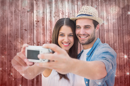 Happy hipster couple taking a selfie against shimmering light design on red photo