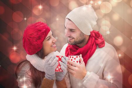 mujer enamorada: Pares del invierno sosteniendo tazas contra dise�o de la luz brillante en rojo