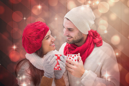 young couple smiling: Winter couple holding mugs against light design shimmering on red