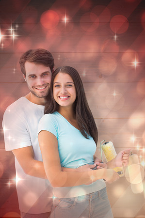 Happy young couple painting together against light design shimmering on red photo