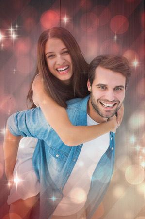 Happy hipster giving his girlfriend a piggy back against light design shimmering on red photo