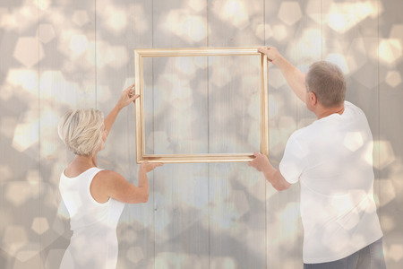 hanging up: Mature couple hanging up picture frame against light glowing dots design pattern Stock Photo