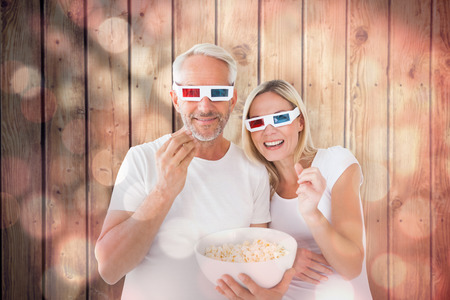 Happy couple wearing 3d glasses eating popcorn against light circles on black background photo