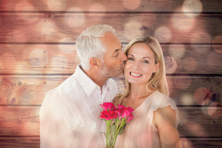 Affectionate man kissing his wife on the cheek with roses against light circles on black background photo