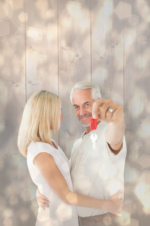 Happy couple showing their new house key against light glowing dots design pattern photo
