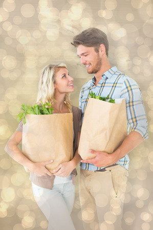 Attractive couple holding their grocery bags against light glowing dots design pattern photo