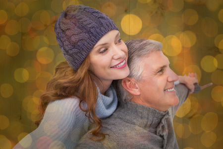 warm clothing: Carefree couple in warm clothing against close up of christmas lights Stock Photo