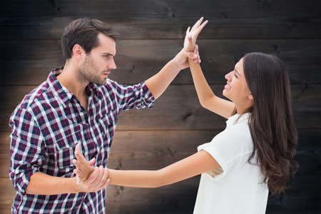 overpowering: Fearful brunette being overpowered by boyfriend against wooden planks background