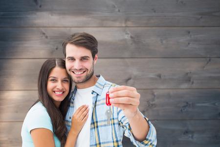parejas jovenes: Feliz pareja joven que sostiene la nueva llave de la casa contra el blanqueado fondo tablones de madera Foto de archivo