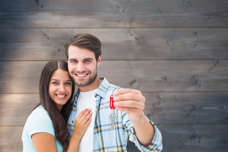 Happy young couple holding new house key against bleached wooden planks background Stock Photo