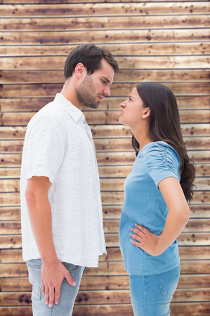 outraged: Angry couple staring at each other against wooden planks