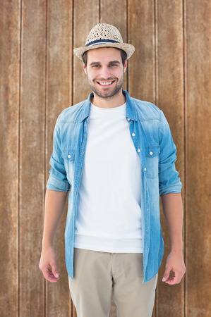 chinos: Handsome hipster smiling at camera against wooden planks background