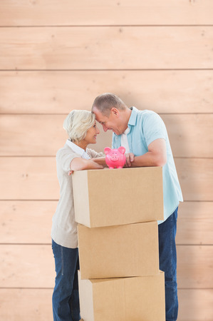 relocating: Older couple smiling at each other with moving boxes and piggy bank against wooden planks