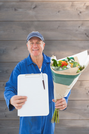 boiler suit: Happy flower delivery man showing clipboard against wooden planks