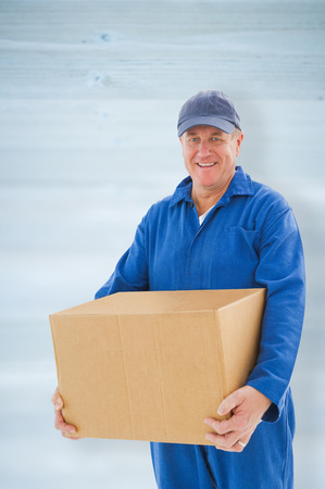 boiler suit: Happy delivery man holding cardboard box against wooden planks