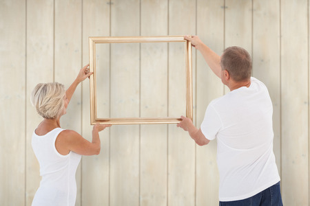 hanging up: Mature couple hanging up picture frame against wooden planks