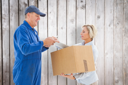 boiler suit: Happy delivery man with customer against wooden planks