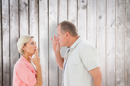 mouth couple: Older couple holding hands to mouth for silence against wooden planks