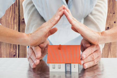home insurance: Couples hands with model house against wooden planks background